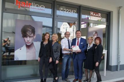 Mit einer Brüder-Grimm-Torte gratulierte OB Claus Kaminsky Friseurmeister Michael Dörr und seinem Team zu Eröffnung des neuen Friseurstudios am Gloria Palais.